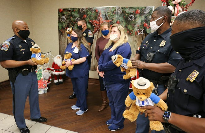 Alabama State Troopers brought teddy bears to DCH Regional Medical Center Thursday, Dec. 17, 2020, for the staff to share with children who are hospitalized to help bring comfort to them. Trooper Reginal King, left, and several other troopers present the teddy bears to nurses. [Staff Photo/Gary Cosby Jr.]