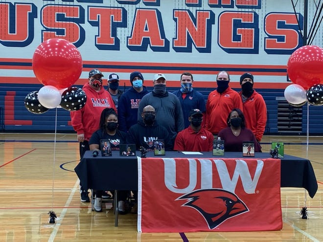 Life Waxahachie senior Jalen Mann poses with family members and coaches after signing a national letter of intent to play NCAA Division I football at University of Incarnate Word in San Antonio. Mann's senior season was limited by injury, but he finished with 422 total yards and five combined touchdowns in six games and was the team's leading scorer with 32 total points. Mann was first-team all-district as a junior.