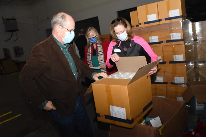 David Britt (left), president of the United Way of Central Louisiana; Suzy Smart, Britt's executive assistant; and Sandra McQuain, England Airpark executive director, look in boxes containing items that Delta Air Lines donated to the United Way of Central Louisiana. The shipment was delivered to a 34,000 square foot warehouse at England Airpark that has served as the staging base for United Way since Hurricane Laura.