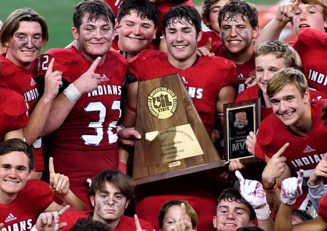 Members of the Jim Ned Indians pose with the Class 3A Division I state championship Thursday at AT&T Stadium. The Indians rallied from a 21-0 deficit to win 29-28 in overtime, going for a two-point conversion and the school's first football title.
