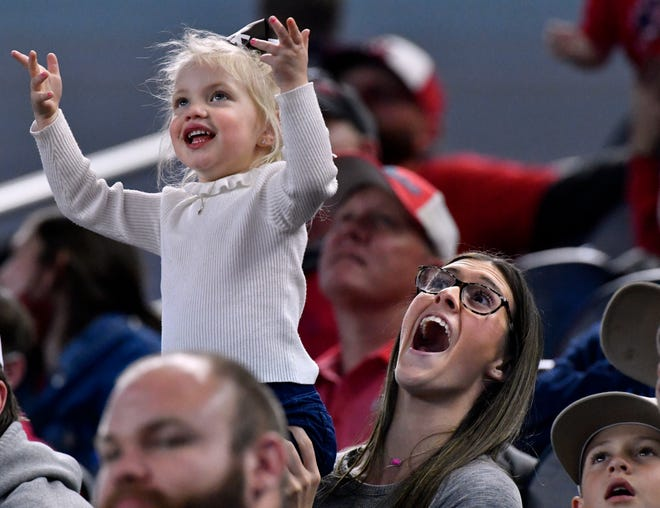 A Jim Ned fan reacts as the little girl she is holding up appears on the overhead screen at AT&T Stadium in Arlington Thursday Dec. 17, 2020. The Indians played Hallettsville in the Class 3A Division I state championship. Final score in overtime was 29-28, Jim Ned.