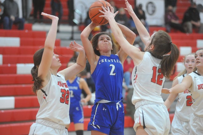 Crestline's Hannah Delong powers up for a shot over Bucyrus' Emma Tyrrell (12) and Lily Neuman (32).