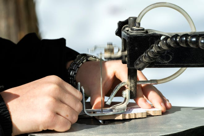 Carson King, 12, works on a New Jersey shaped ornament at his home in Luberton, N.J.