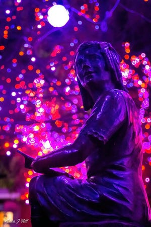 A statue of a young girl is illuminated at the 2020 PNC Festival Lights at the CIncinnati Zoo and Botanical Garden. USA Today picked Cincinnati's festival as best zoo lights for a third year in a row in 2020.
