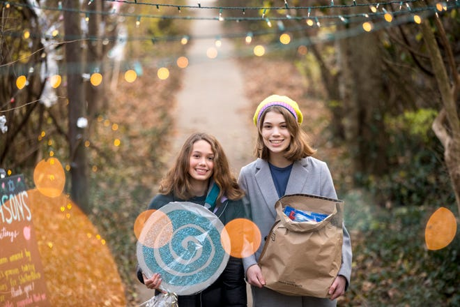 """Iris Weizer, 12, and her sister, Lauren, stand on a sidewalk where they have strung Christmas lights on Friday, Dec. 18, 2020 in Hyde Park. The """"Winter Wonderland"""" was set up to collect items for Cincinnati's homeless. The Weizer's have a collection spot and will be collecting donations through Christmas."""