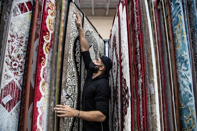 Nash Alnashi, store manager of Nice Price in Dearborn arrange the rugs at the store on Dec. 18, 2020.