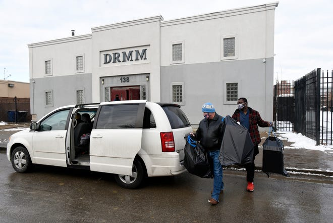 Volunteer Joseph Fuoco, front, and other volunteers place gifts in the cars of people in need outside the Detroit Rescue Mission Ministries in Detroit.
