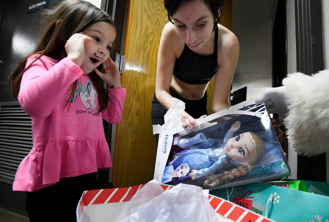 """Ember Oglesby, 4, and mother Katie are happy to pull out an Elsa doll, from the movie """"Frozen"""" from bags of presents."""
