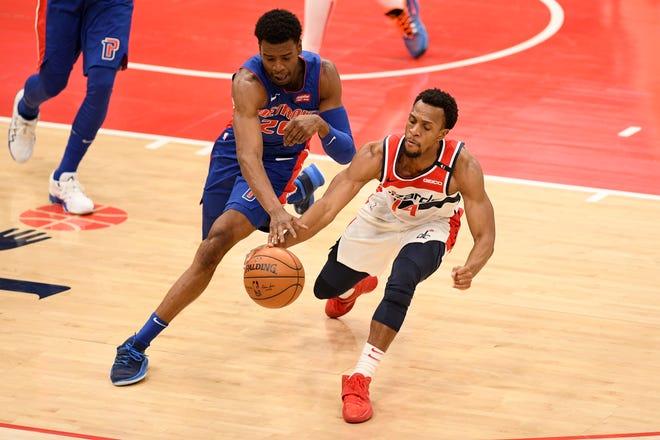 Guard Pistons Josh Jackson, kiri, bertarung memperebutkan bola di samping guard Wizards Ish Smith pada Kamis malam.