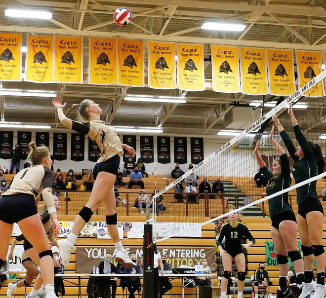Helena Capital's Paige Bartsch goes high to hammer a kill attempt over the outstretched arms of C.M. Russell defenders Natalie Bosley and Lauren Lindseth during last month's Class AA state volleyball championship match in Helena.