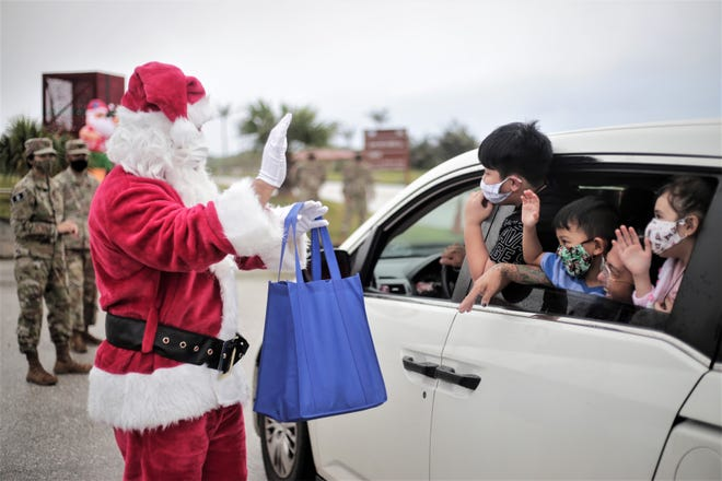 Santa delivers gifts to Guam Air National Guard families at a holiday gift drive-thru on Andersen Air Force Base Dec. 12 2020.