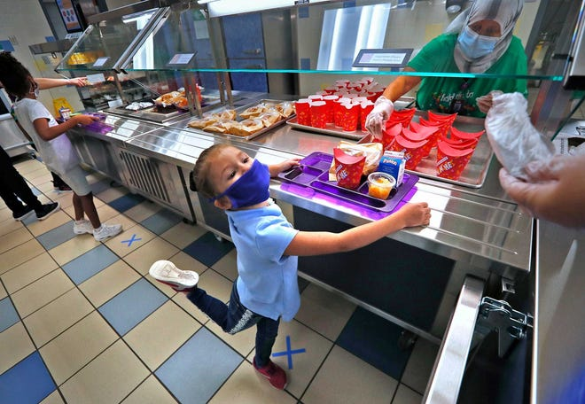 Students go through the lunch line at Garden City Elementary School, Tuesday, Aug. 18, 2020. Because of the COVID-19 pandemic, extra safety precautions are in place, including individually wrapping the food and social distancing with the help of Xs on the floor for guidance.
