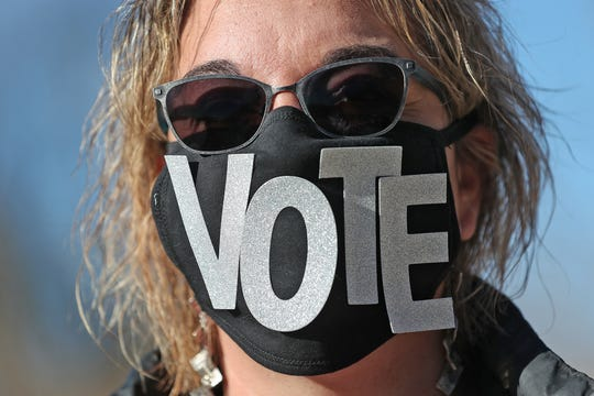Chris Dotson, 52, Westfield, gives the message to vote, as she dose last minute campaigning on Election Day outside the Cool Creek Nature Center voting site, in Westfield, Tuesday, Nov. 3, 2020.