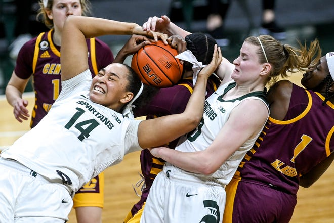 Michigan State's Taiyier Parks, left, tangles with Central Michigan's Jahari Smith, center, and teammate Julia Ayrault while going for a rebound during the second quarter on Friday, Dec. 18, 2020, at the Breslin Center in East Lansing. At far right is CMU's Micaela Kelly.