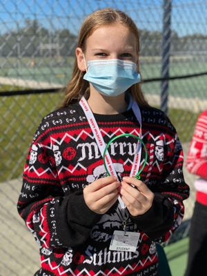 Seventh-grade student Courtney Crown and her entrepreneurial team's product, the mask band. The team presented and sold their product at the marketplace at North Naples Middle School on Dec. 18.