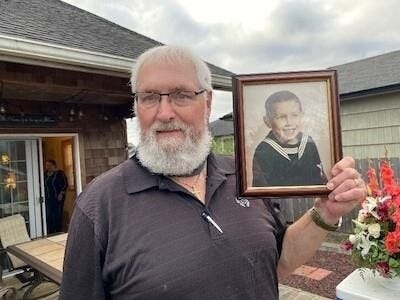 Bill Trumbull, holding a picture of his younger self.