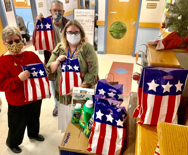 DAR Service to Veterans Committee Chair Beth Wallace (in red) is pictured with Veteran John Mioni and Kat McClure of Mesilla Valley Community of Hope with gift bag donations for homeless veterans.