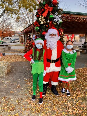 """Santa Marty Martinez and his elves, daughter Sarii Martinez, 11, and niece Jenica Sanchez, 9, wore masks at this year's """"Small Town Christmas"""" celebration in Miami, Arizona, on Dec. 12, 2020."""