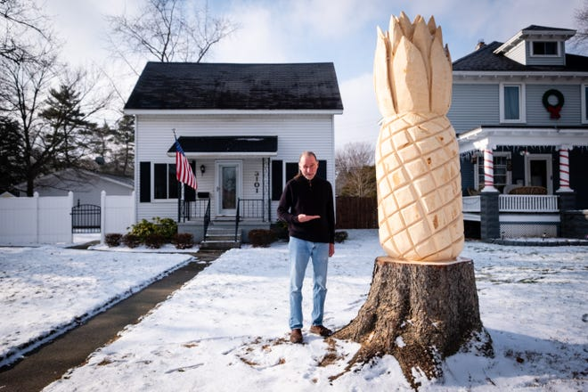 Don Cole says welcome in sign language while standing next to a giant pineapple he had carved in what was left of a fallen tree Friday, Dec. 18, 2020, in the front lawn of his Gratiot Avenue home. The pineapple represents hospitality and welcoming.