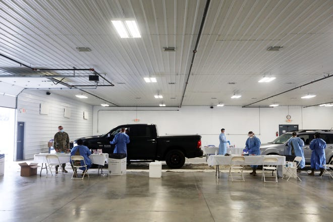 Medics with the Ohio Army National Guard and Air National Guard adminstered tests for COVID-19 during a drive-thru testing event at the Muskingum County Fairgrounds on Friday.