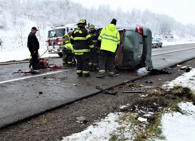 Members of the Perry Township and New Concord Fire Departments work on extricating the driver from a one-car crash on Friday afternoon on Interstate 70 West. The driver was the lone occupant and taken to Genesis with non-life-threatening injuries.