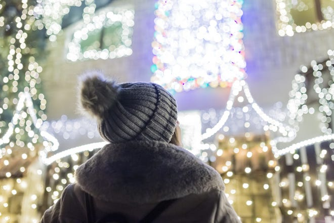 Young Woman Looking At House Decorated With Christmas Lights