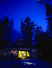 A yurt provides a cozy winter camp shelter and a view of a dazzling night sky on Minnesota's Gunflint Trail.