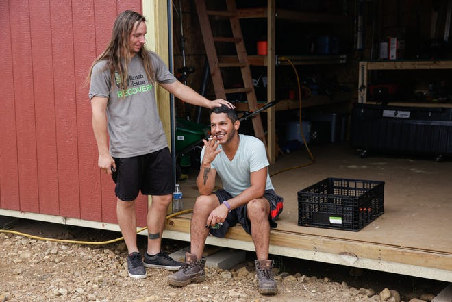 """Residents Chris Weber, 29, left, and Pablo Quintero, 29, take a break after harvesting vegetables at Simple Promise Farms in Elgin, Texas on Friday, Nov. 13, 2020. Quintero said when he arrived to the program he was fearful that no one would accept him. """"Being a person of color and being Queer as well I was scared because in treatment places I know it's all going to be cisgender, white males,"""" he said. """"The guys have really proved me wrong."""""""
