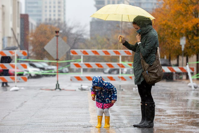 Cannon Cluley, 2, jumps in a rain puddle as her mother Wendy shops during the Sustainable Food Center's farmers market located on the streets of Guadalupe and West Fourth in downtown Austin on Saturday, Dec. 19, 2020.