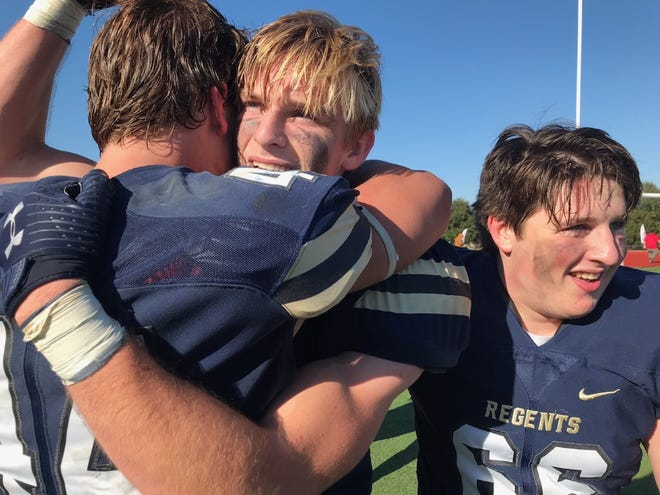 Regents senior Ben Buerkle, center, celebrates the state championship with teammates Charles Benson (44) and Isaac Lipton after his interception return for the winning touchdown on the final play.