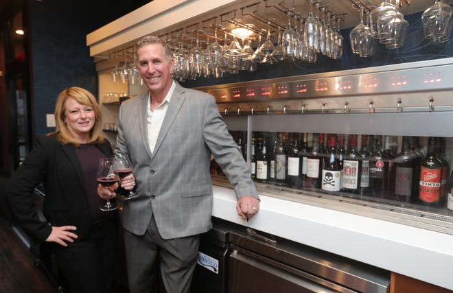 Vinifera Wine To Whiskey Bar owners Michelle and John Bisson are pictured inside their business at 3236 State Road on Friday, Dec. 11, 2020 in Cuyahoga Falls, Ohio. [Phil Masturzo/ Beacon Journal]