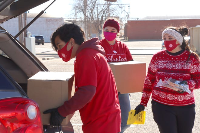 Nicholas Smith, Jeanette Camarena and Christina Espino load boxes of food for a participant in the USDA's Farmers to Families Food Distribution in conjunction with the Northside Toy Drive distribution day Saturday. [Neil Starkey / For the Amarillo Globe-News]