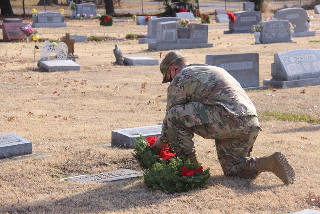 Oklahoma National Guard Major Rufus Reed places a wreath at the grave of a veteran Saturday morning. Reed joined several others in honoring veterans during the Wreaths Across America ceremony in Davis.