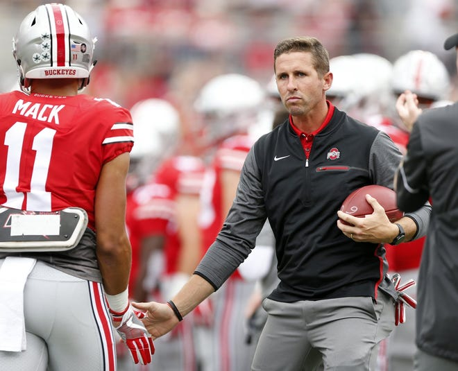 Former Ohio State Buckeyes wide receiver Brian Hartline, who now helps the team as a quality control assistant, high fives wide receiver Austin Mack (11) prior to the NCAA football game against the Army Black Knights at Ohio Stadium in Columbus on Sept. 16, 2017. Ohio State won 38-7. [Adam Cairns / Dispatch]