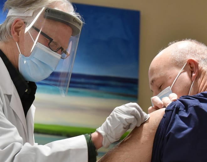 Registered nurse Fred Allen injects a dose of COVID-19 vaccine for registered nurse Mike McGrail at the Spaulding Rehabilitation Hospital in Sandwich on Friday.