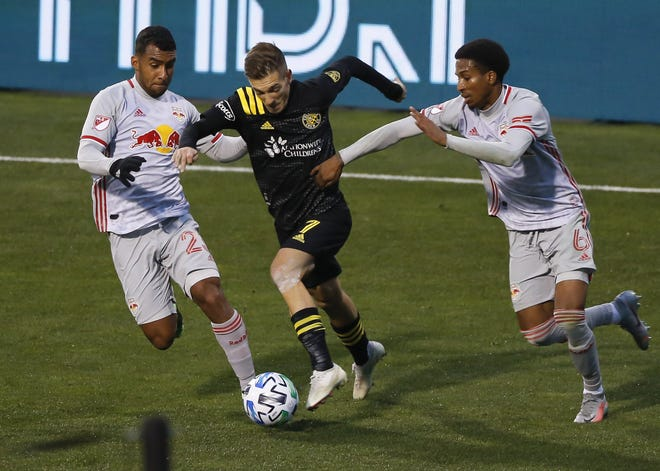 The Crew's Pedro Santos dribbles between the Red Bulls' Cristian Casseres Jr., left, and Kyle Duncan during a playoff game on Nov. 21. Santos sat out the Crew's victory over the Seattle Sounders in the MLS Cup final after testing positive for COVID-19.
