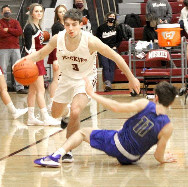 John Glenn's Blade Barclay (3) dribbles the ball past Maysville's Cole Roberts (11) during MVL action on Friday night at John Glenn High School. The Muskies celebrated Senior Night with their first win of the season, 55-42 over the Panthers.