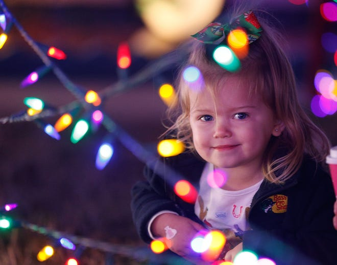 Two-year-old Ella Moore marvels at the Christmas light display at the Twi-Light II Hotel in Holly Hill, Thursday, Dec. 17, 2020.