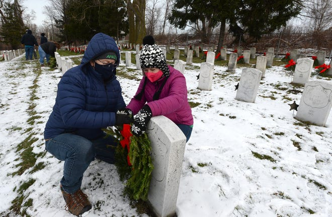 Jack Campbell and Sheri Campbell of Millcreek Township place a wreath on a gravestone at the Pennsylvania Soldiers' & Sailors' Home, Veterans Memorial Cemetery in Erie on Saturday. The couple was volunteering for the annual National Wreaths Across America Day event that honors veterans.