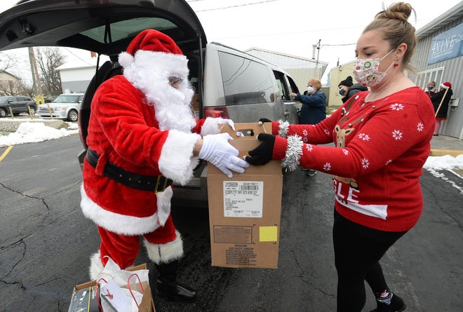 Carl Voltz, left, dressed as Santa Claus, and Jessica George of the Skunk & Goat Tavern hand out boxes of food and presents and gift cards Saturday outside the 4 N.I.N.E. Thrift Store in North East.