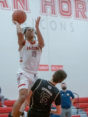 Van Horn guard Jaden Monday (11) leaps to put up a shot against William Chrisman defender Trey Kates (15) in Friday's game at Van Horn. Monday made some key free throws down the stretch and finished with a game-high 16 points to lead the Falcons to a 61-57 win.
