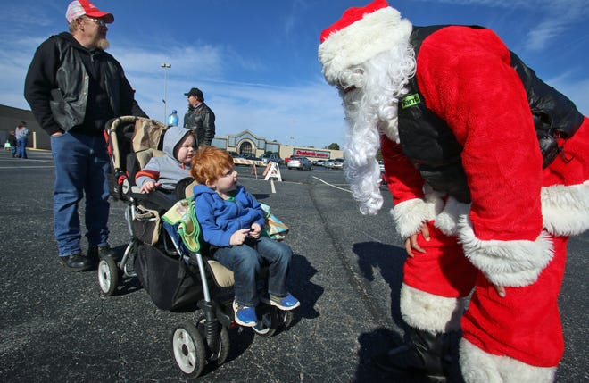 Three-year-old Luke Logan and his brother, Levi Logan, 2, along with their dad, Mark Logan, meet Santa as more than 100 people took part in the 32nd Annual Windjammers Toy Run which began in the parking area of the Cleveland Mall in Shelby Saturday, Dec. 19, 2020.