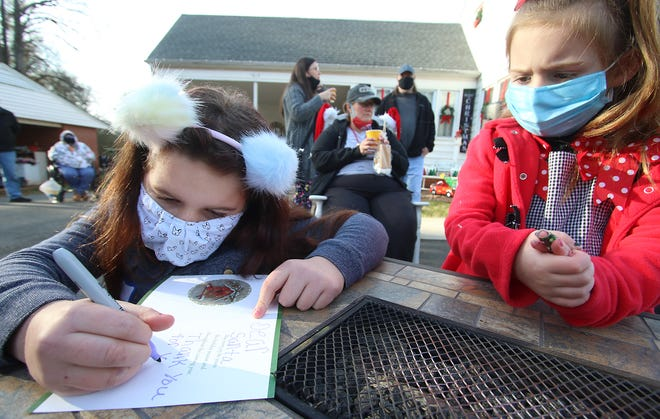 Nine-year-old Millie Goff writes a note to Santa as neighbors gathered on the front yard of Donna Norman's home on Spencer Mountain Road in Ranlo where a special Christmas event was held Saturday afternoon, Dec. 19, 2020.
