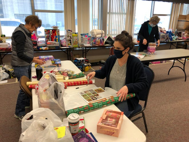 Lavon Weber, left, Starla Gano, center, and Roselin Pfeifer on Saturday volunteered to wrap scores of toys and other items donated to the Salvation Army's Angel Tree program for the needy in Ellis County.