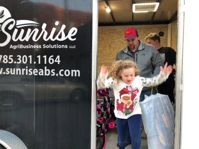 Marci Brunner jumps from the trailer she was helping her dad, Travis Brunner, center, and her brother, Easton, fill with toys and food baskets on Friday.