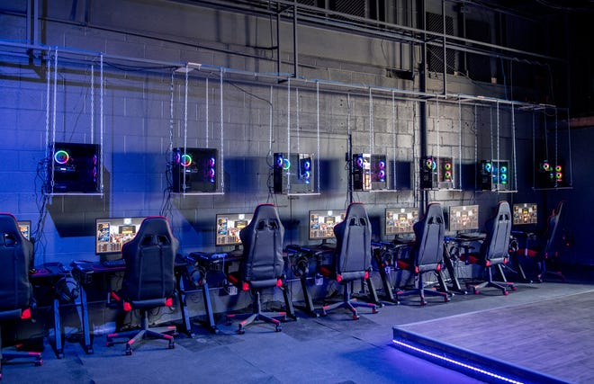 Gaming PCs sit on platforms hanging from chains above monitors and keyboards along a concrete block wall at Arena Esports gaming lounge, 318 S. Main St., in Morton.