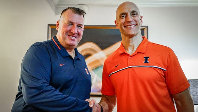 Illinois football coach Bret Bielema, left, shakes hands with athletic director Josh Whitman. The Big Ten Conference school on Saturday hired Bielema, the former Wisconsin and Arkansas coach.