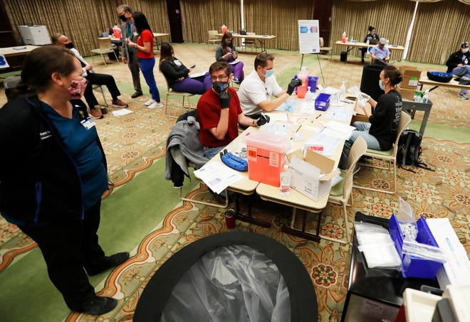 UMC pharmacists prepare vaccinations before administering them to doctors and nurses. University Medical Center started their first COVID-19 vaccinations Friday, Dec.18 at the McInturff Conference Center at UMC. (Mark Rogers/For A-J Media)