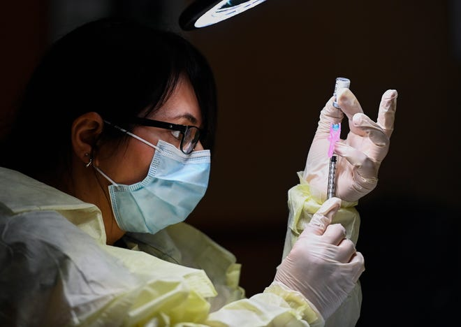 Francesca Paceri, a registered pharmacist technician, carefully fills the Pfizer-BioNTech COVID-19 mRNA vaccine at a clinic in Toronto. Toronto and Peel region continue to be in lockdown.