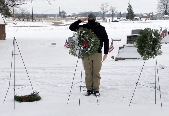 Sgt. Ben Mitchell salutes after placing a wreath dedicated to the missing in action and prisoners of war, during Wreaths Across America Day on Saturday at South Farmington Friends Cemetery.